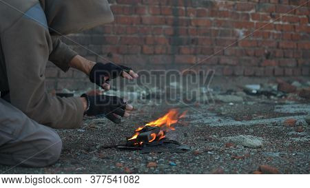 Shaking With Cold. Homeless Man Warms His Hands. A Homeless Man Warms His Hands By The Fire. Post-ap