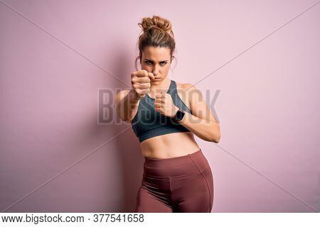 Young beautiful blonde sportswoman doing sport wearing sportswear over pink background Punching fist to fight, aggressive and angry attack, threat and violence