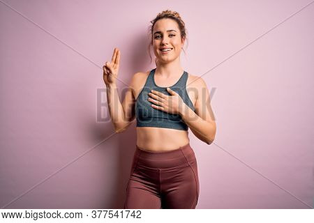 Young beautiful blonde sportswoman doing sport wearing sportswear over pink background smiling swearing with hand on chest and fingers up, making a loyalty promise oath