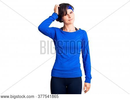 Beautiful young woman with short hair wearing training workout clothes confuse and wondering about question. uncertain with doubt, thinking with hand on head. pensive concept.