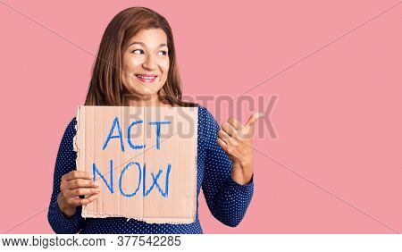 Middle age latin woman holding act now banner pointing thumb up to the side smiling happy with open mouth