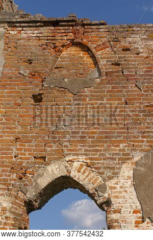 The Ruined Gothic Vault Of The Old Catholic Chapel. The Ruins Of An Old Church. Brick Wall And Blue