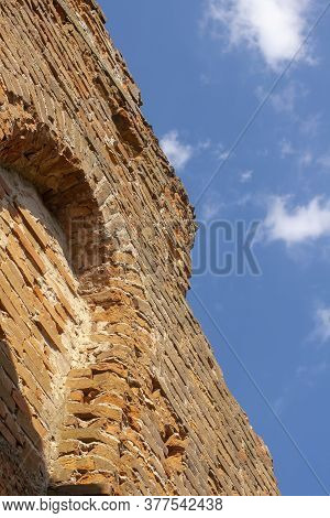 The Ruined Wall Of The Old Catholic Chapel. The Ruins Of An Old Church. Brick Wall En Blue Sky Backg