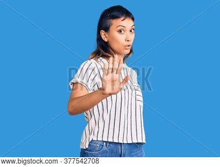 Young woman wearing casual clothes moving away hands palms showing refusal and denial with afraid and disgusting expression. stop and forbidden.