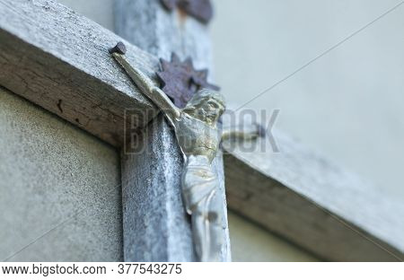 Wooden Crucifix On The Wall Closeup. Image Of Jesus. Horizontal Photography With Unfocused Distant P