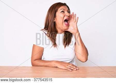 Middle age brunette hispanic woman wearing casual white tshirt sitting on the table shouting and screaming loud to side with hand on mouth. communication concept.