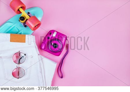 Summer Fashion Flatlay With White Denim Jeans, Turquoise Penny Skateboard, Purple Instant Camera And
