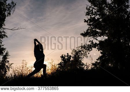 Silhouette Of Woman Practicing Yoga Asana Pose Of Warrior In Evening At Sunset. Girl Yoga Instructor