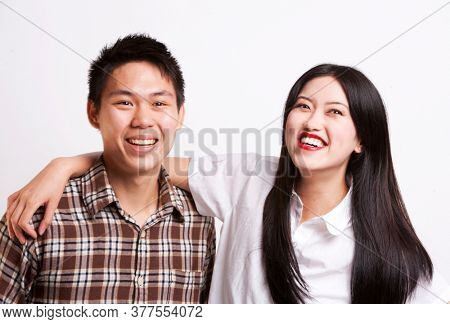 Portrait of young Asian friends smiling together over white background