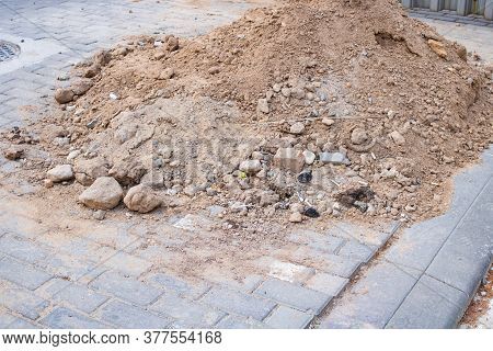 Pile Of Construction Sand On Tiled Sidewalk