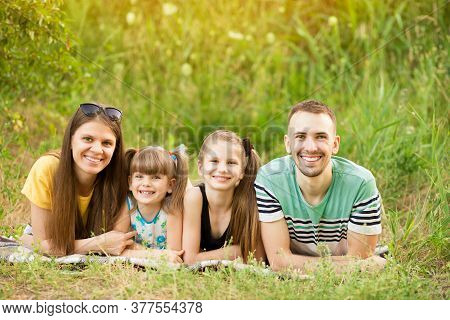 Cheerful Family Of Four In Summer Park, Dad, Mum And Heir Two Lovely Daughter Lying On Grass