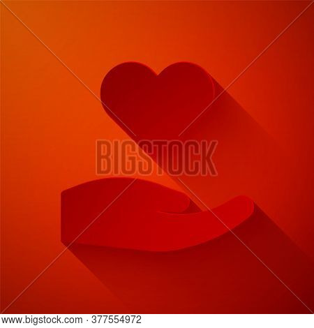 Paper Cut Heart In Hand Icon Isolated On Red Background. Hand Giving Love Symbol. Valentines Day Sym