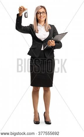 Full length portrait of a woman in formal clothes holding a car key and smiling isolated on white background