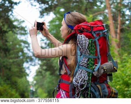 A Girl With A Backpack In The Forest Makes A Photo With Her Phone. Ecotourism Concept.