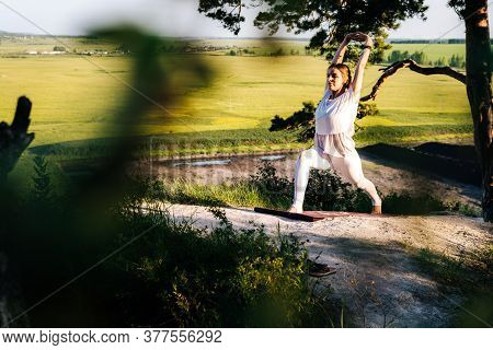 Concentrated Young Woman Doing Warrior Yoga Asana Pose On Top Of Rock Background Of Beautiful Landsc