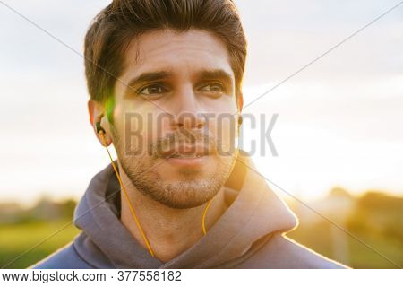 Image of athletic bristle sportsman using earphones and looking aside outdoors