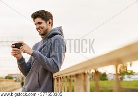 Image of smiling man with earphones playing video game on cellphone while leaning on railing outdoors