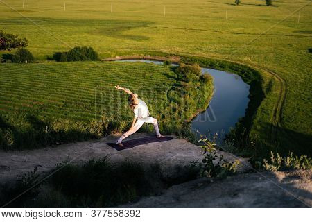 Concentrated Young Caucasian Woman Is Performing Warrior Yoga Asana Pose On Top Of Rock Background O