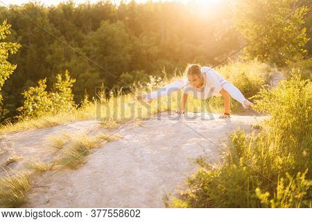 Beautiful Sporty Woman Performing Firefly Pose. Girl Doing Advanced Yoga Exercises, Leaning On Hands