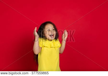 Astonished. Beautiful Little Girl Isolated On Red Background. Half-lenght Portrait Of Happy Child Ge