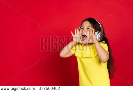 Shouting For Sales, Wearing Headphones. Beautiful Little Girl On Red Background. Half-lenght Portrai