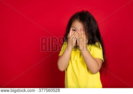 Scared Hiding Face With Hands. Beautiful Little Girl On Red Background. Half-lenght Portrait Of Happ