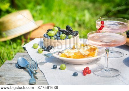 Outdoor Summer Lifestyle With A Gourmet Picnic Laid Out In A Garden With Berries, Pie And Pink Drink