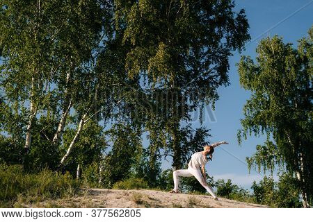 Sporty Young Woman Doing Yoga Warrior Pose On Clear Sunny Day At Nature. Pretty Yoga Instructor Is P