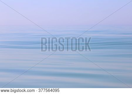Calm Sea Wavy Surface Of The Sea Under A Clear Sky Close-up. Blue Background.