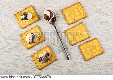 Few сrackers With Chocolate-dairy Paste, Teaspoon With Paste On Light Wooden Table. Top View