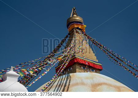 Boudha Stupa, At Kathmandu In Nepal Against Blue Sky, With Religious Colorful Flags Waving.