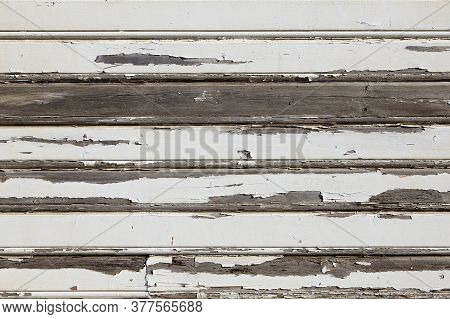 The Texture Of The Wall, Sheathed With Wooden Slats With Peeling White Paint. Low Contrast Backgroun