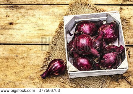 Whole Unpeeled Purple Onion In A Wooden Crate