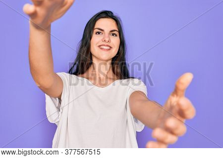 Young beautiful brunette woman wearing casual white t-shirt over purple background looking at the camera smiling with open arms for hug. Cheerful expression embracing happiness.