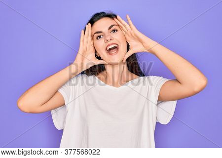 Young beautiful brunette woman wearing casual white t-shirt over purple background Smiling cheerful playing peek a boo with hands showing face. Surprised and exited
