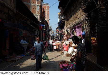 Kathmandu, Nepal - June 17, 2019: Local daily life on street, Sun shining on nepali man with shopping bags walking on narrow street in old town