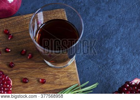 Pomegranate Juice With Pomegranate On A Wooden Board On A Blue Background. Natural Drink With Rosema