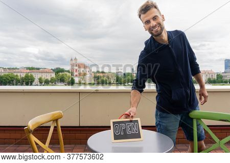 Handsome Man Putting Chalkboard With Word Open On Table In Open-air Cafe. Smiling Waiter Holding Sig