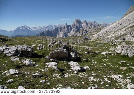 Views Of The Mountain Range, The Italian Dolomites On A Background Of Blue Sky With Meadows And Flow