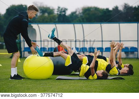 Young Soccer Players In Team On Training With Coach. Boys Training With A Gym Ball. Stability Traini