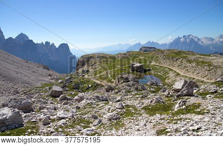 Mountain Footpath Lined With A Meadow With Flowers On The Background Of A Mountain Massif With Blue