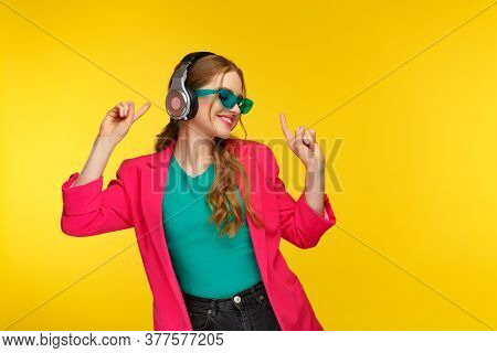 Enjoy Listening To Music. Young Redhead Woman In Headphones Listening Music. Funny Smiling Girl In E