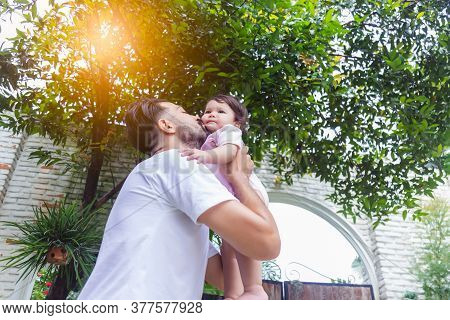 Happy Handsome Father Kissing Adorable Little Baby Daughter With Happiness And Smile Face. Single Da