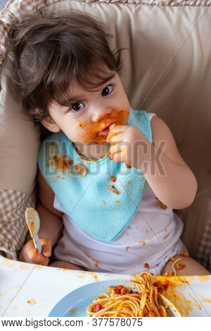 Adorable Little Toddler Girl Or Infant Baby Eating Delicious Food With Tomato Sauce And Sucking Thum