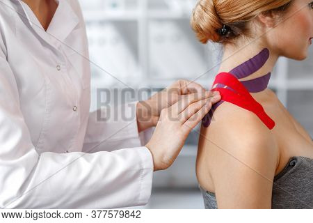 Kinesiology Taping. Physical Therapist Applying Kinesiology Tape To Patient Neck. Therapist Treating