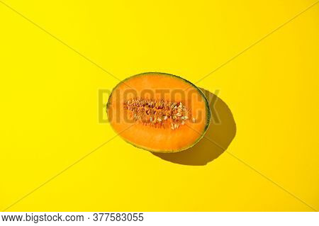 Melon In Harsh Sunlight On A Yellow Background. Juicy Ripe Summer Fruit. Free Space For Text. High Q
