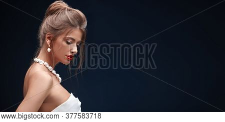 Portrait of a gorgeous brunette woman with evening make-up and hairstyle wearing luxury pearl jewelry on a dark blue background. Beauty, fashion. Copy space.