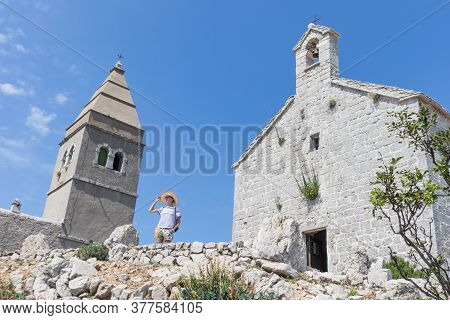 Female Traveler Sightseeing In An Ancient Costal Village Of Lubenice On The Island Of Cres, Croatia