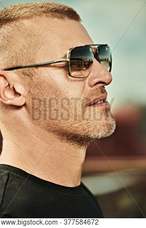 Portrait of a handsome brutal mature man with short hair and bristles wearing trendy sunglasses against the backdrop of a big city. Men's style. Optics for men.