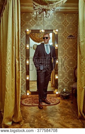 Full length portrait of a smiling wealthy mature man in an elegant suit and modern sunglasses in a luxury apartment. Male beauty, fashion. Optics, sunglasses for men.